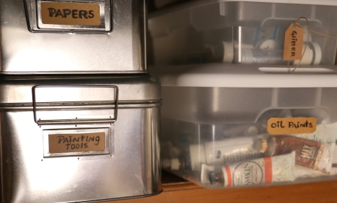 Organized, labeled art supplies in clear containers.
